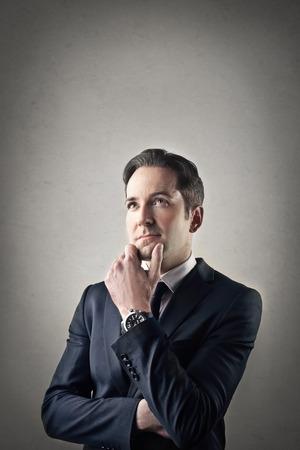 businessman thinking: Doubtful businessman thinking