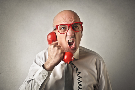 the boss: Angry man holding a red phone