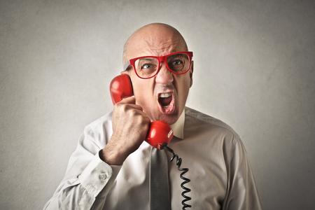 patron: Hombre enojado que sostiene un teléfono rojo