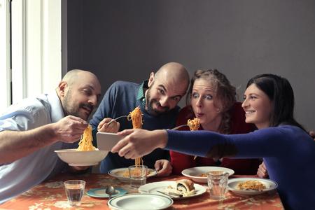 plato del buen comer: Amigos que comen las pastas Foto de archivo