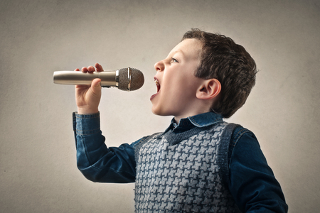 boy kid: Young singer with a microphone Stock Photo