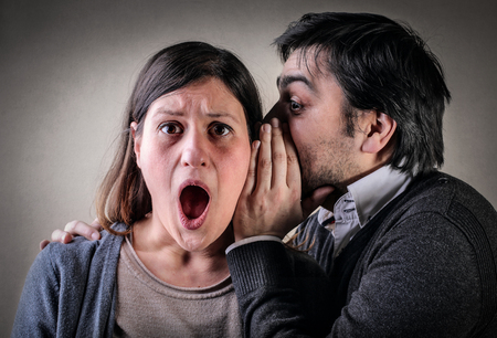 accusations: Man whispering into a womans ear Stock Photo