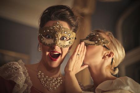 hallooween: Masked women whispering Stock Photo
