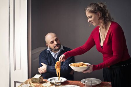 Woman serving pasta to her husband