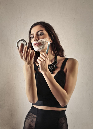 conceit: Beautiful woman shaving her face Stock Photo