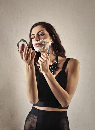 Beautiful woman shaving her face Stock Photo