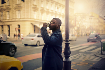 african business: Businessman drinking in the street