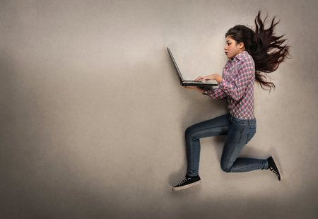 girl with laptop: Girl jumping with her laptop