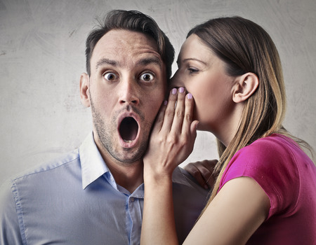 Woman whispering into a mans ear Stock Photo