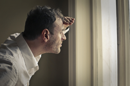 opportunity discovery: Man looking out of the window Stock Photo