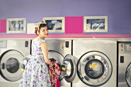 lavadora con ropa: Mujer que hace la colada en un sitio de la vendimia Foto de archivo