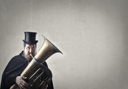 white hat: Chubby man playing trombone Stock Photo