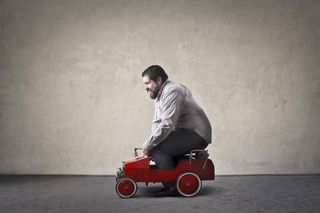 Chubby man het besturen van een speelgoed auto Stockfoto
