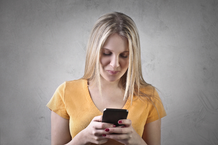 writes: Blonde woman using her smartphone