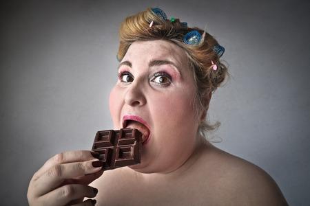 Chubby woman eating chocolate Standard-Bild