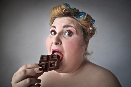 Mollige vrouw die chocolade eet Stockfoto