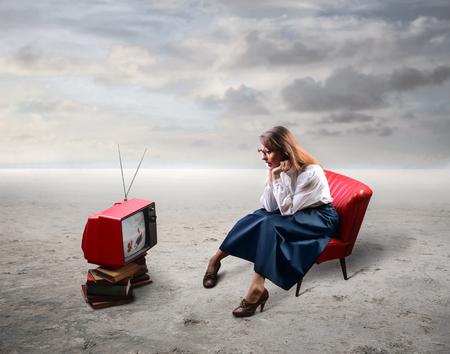 enfado: mujer elegantemente vestida que ve la TV