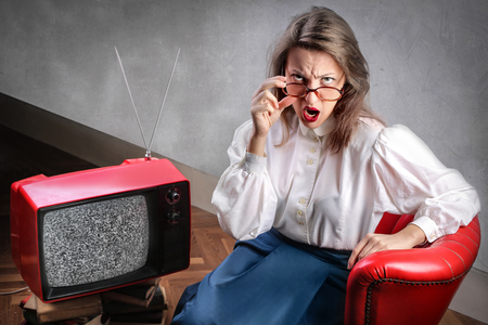willing: Angry woman willing to watch the tv Stock Photo