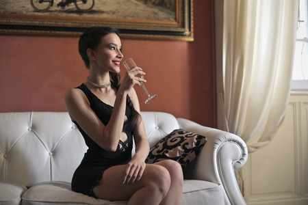 rich people: Woman in a luxury room drinking wine Stock Photo