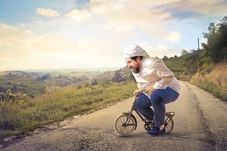 Cook riding a small bike Stockfoto