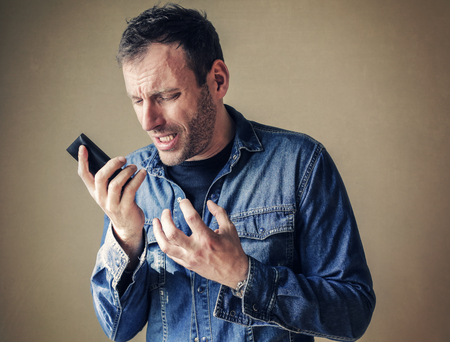 indignant: Disappointed man holding his phone