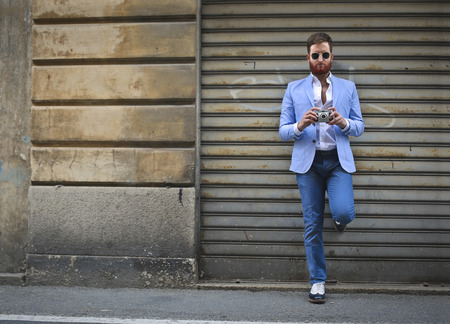 L'homme dans des vêtements élégants en utilisant un téléphone intelligent