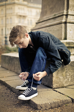 blonde teenager: Teenager adjusting his shoes