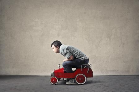 Guidare una macchina giocattolo rosso Archivio Fotografico - 59829029