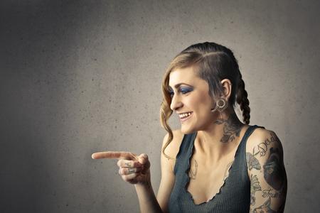 jovenes felices: Mujer tatuada apuntando a alguien