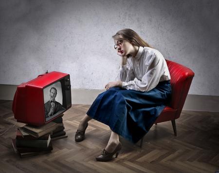 mujer viendo tv: Mujer aburrida que ve la TV