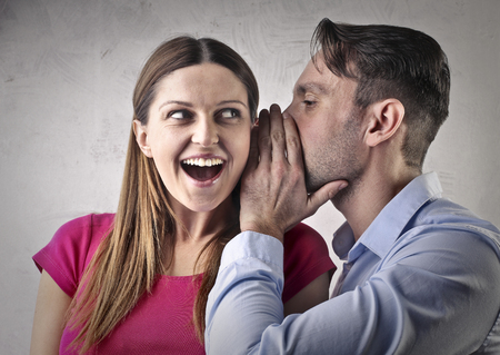 Man whispering into a womans ear Stock fotó