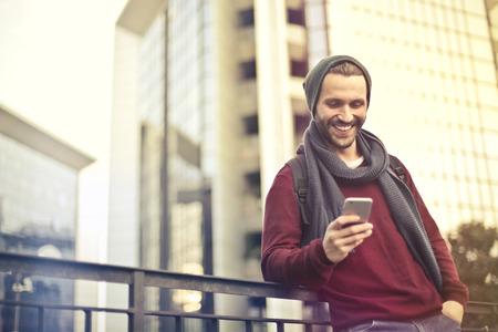 Knappe man met behulp van zijn smartphone