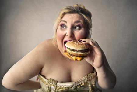 mujeres gordas: Mujer rechoncha que come una hamburguesa