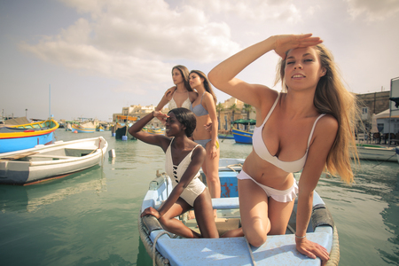 relaxing beach: Beautiful girls on a little boat Stock Photo