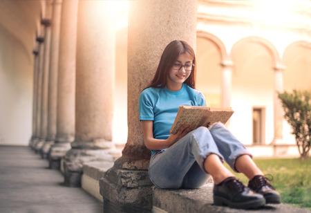 Een boek lezen op de binnenplaats van de universiteit