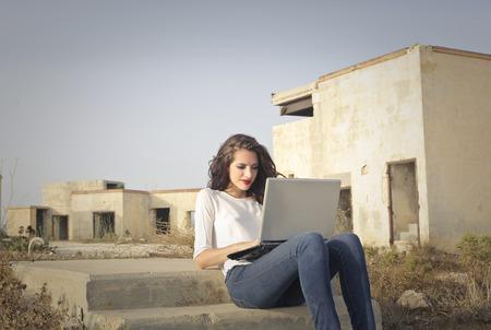 mujeres sentadas: Mujer utilizando un ordenador portátil