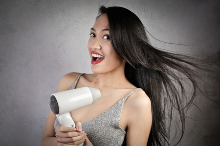 dryer: Woman using a hair dryer