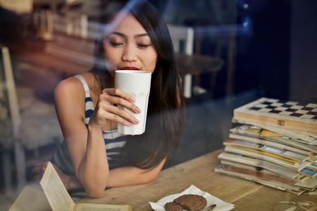 galletas: Chica en el café que bebe una bebida caliente Foto de archivo
