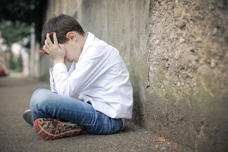 Sad kid sitting on the ground Stock Photo