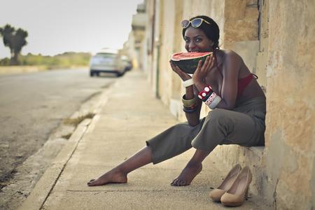 Bella ragazza che mangia una fetta di anguria