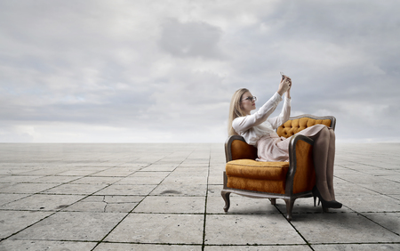 blonde woman: Blonde woman sitting in a luxury armchair Stock Photo