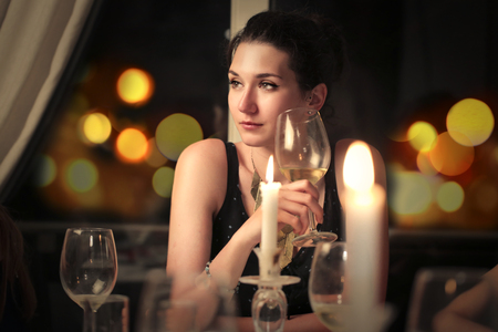 Young lady drinking a glass of wine photo