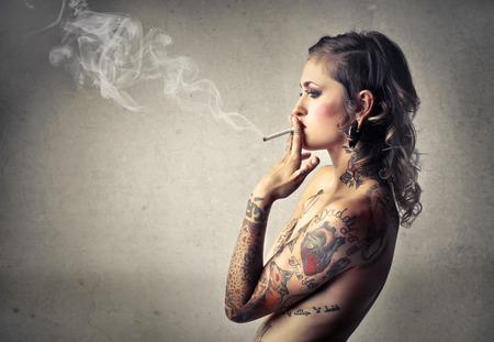 mujer sexy desnuda: Mujer tatuada fumar Foto de archivo