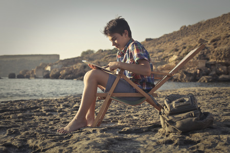 Teenager sitting in a beach chair Stock Photo