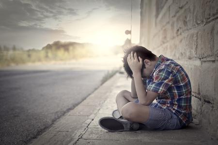 niños tristes: niño triste que se sienta en el suelo