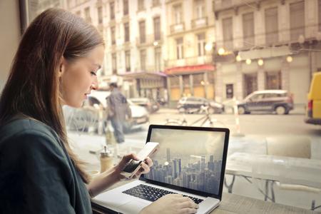 若い女性がカフェで技術を使用して 写真素材