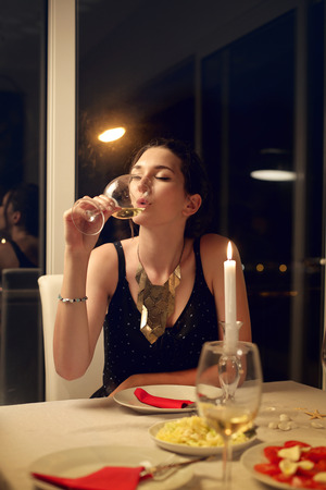Woman drinking a glass of wine photo
