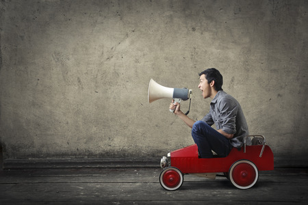 Young man with megaphone driving a toy car