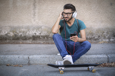 young male: Skater listening to music