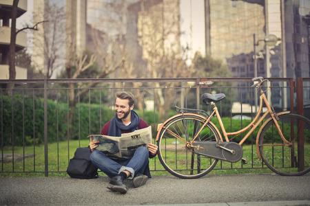 L'homme assis sur le sol en lisant un journal